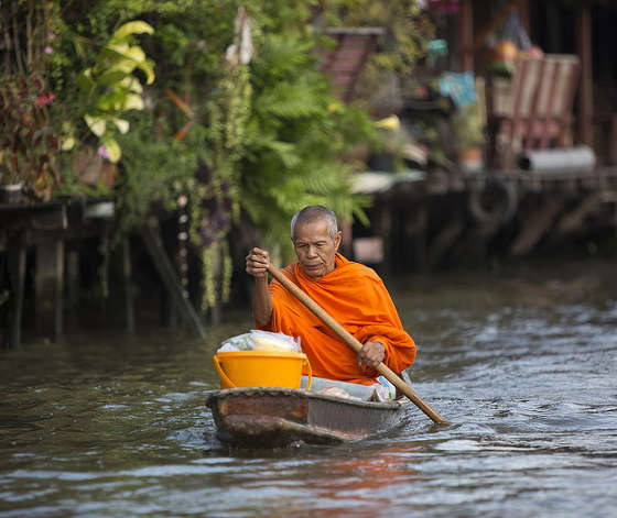Buddhist monk does his alms round on a small boat in Thailand.