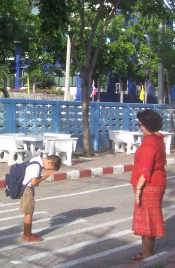Buddhist child is greeting his teacher in Thailand