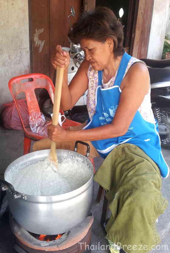 An old Thai woman is preparing Thai steamed sticky rice dessert.