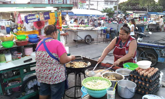 Two Thai ladies prepare phad Thai at a night market.