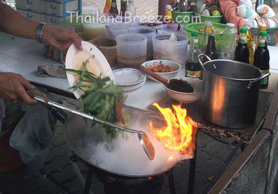 Cooking water spinach on very high heat in Thailand.