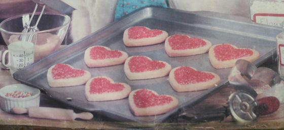 A tray of beautiful home made cookies that are heart shaped.