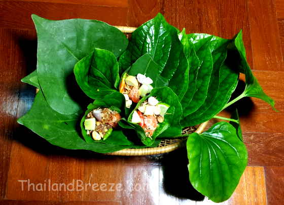 Miang kham is a traditional Thai snack that is wrapped in a leaf.