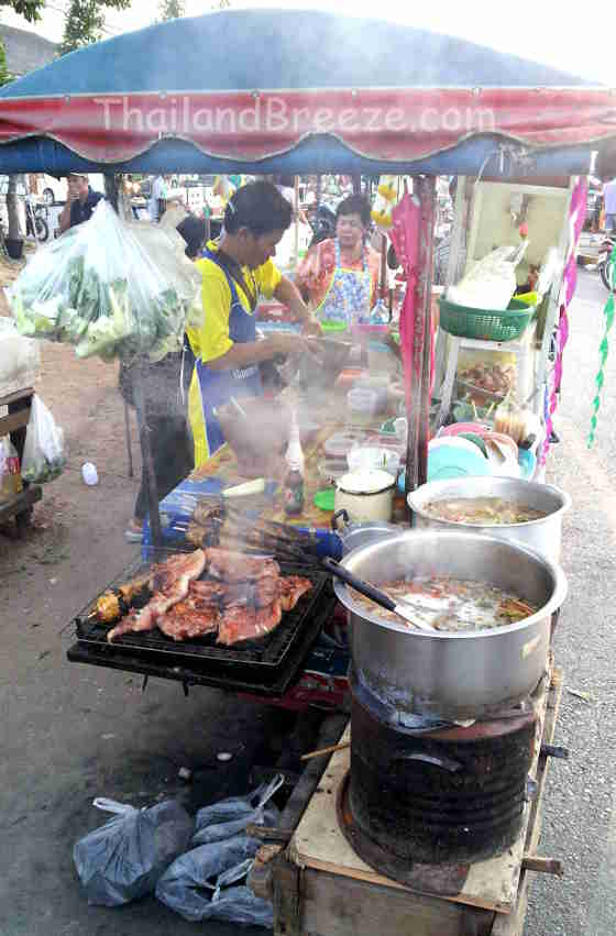 A Thai vendor at a night market grilling pork for north-eastern dishes.