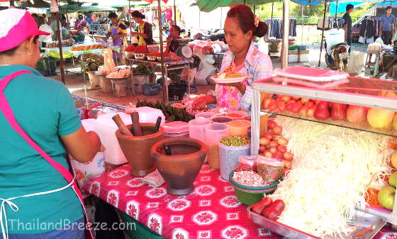 A vendor at a weekly local market in Thailand selling papaya salad.