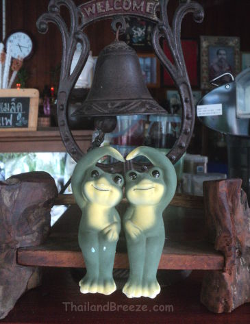Two ceramic frogs in Thailand making the sarang hae yo hand gesture.