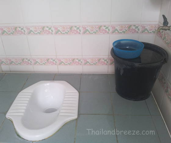 A typical Thai squat toilet with a water bucket and a scoop.