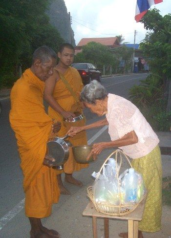 Thais give food during alms round in Thailand