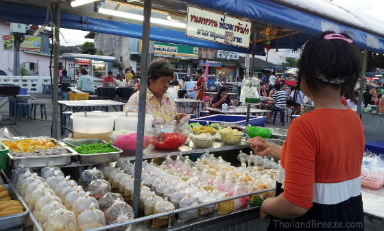 Rows of Thai desserts in plastics bags at a night market.