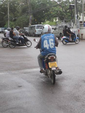 In Thailand the motorcycle taxi drivers wear colorful vests with numbers on the back