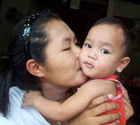 A mother in Thailand sniff kissing her baby