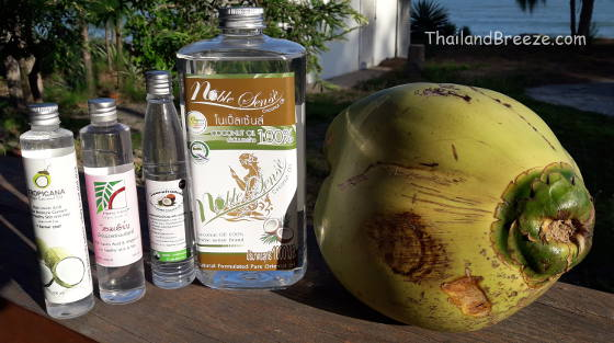 Virgin coconut oil bottles and a cooking coconut in Thailand.